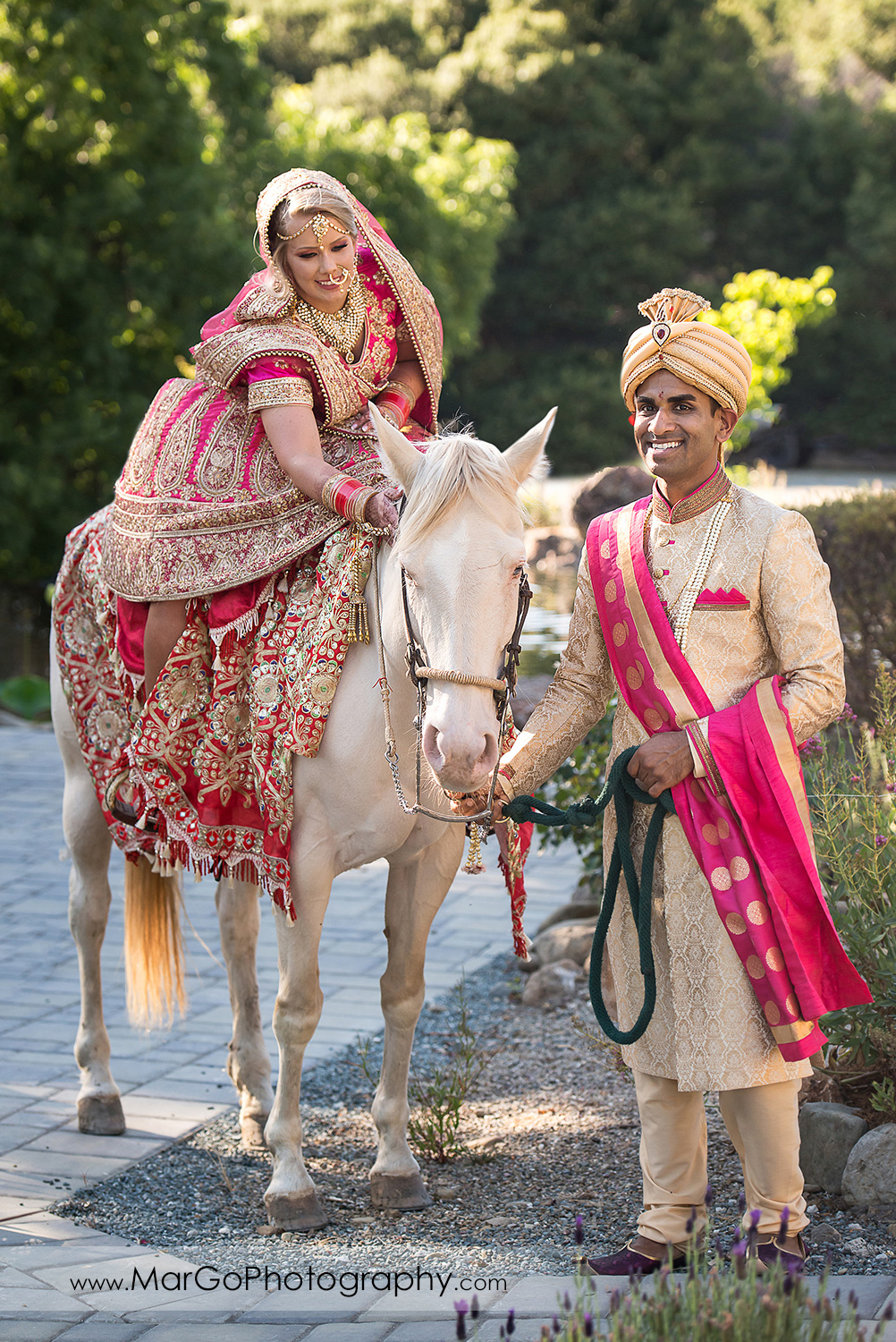Indian bride on the white horse led by groom at Elliston Vineyards in Sunol