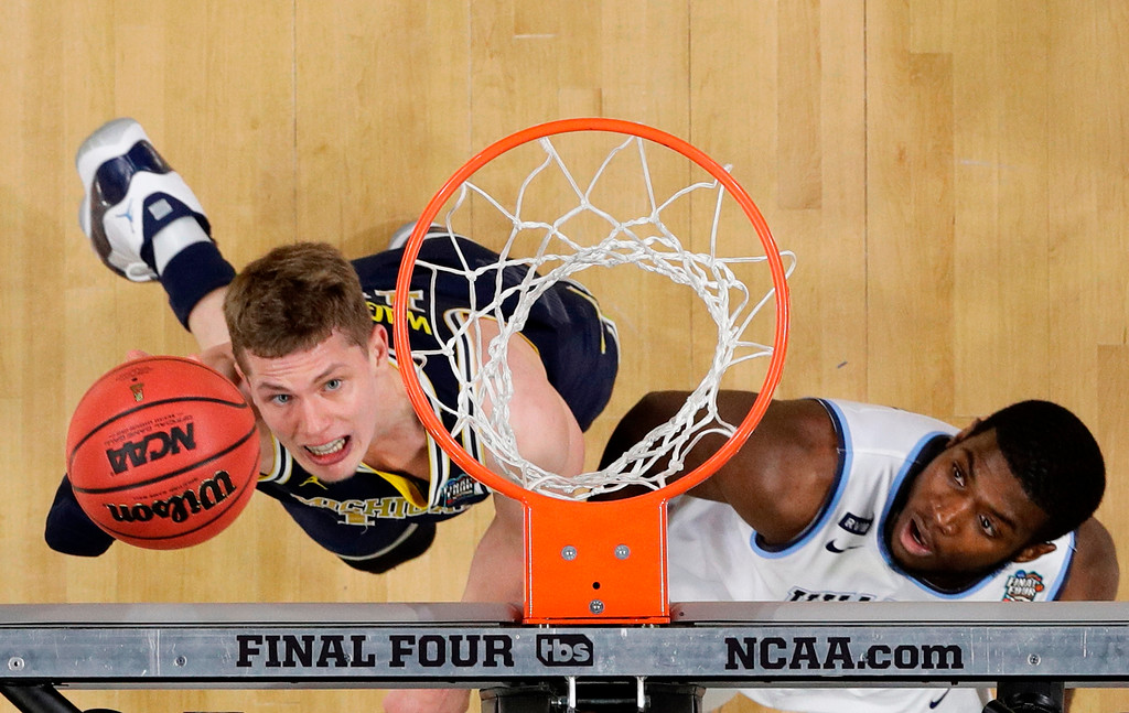 . Michigan forward Moritz Wagner, left, drives to the basket over Villanova forward Eric Paschall during the first half in the championship game of the Final Four NCAA college basketball tournament, Monday, April 2, 2018, in San Antonio. (AP Photo/David J. Phillip)