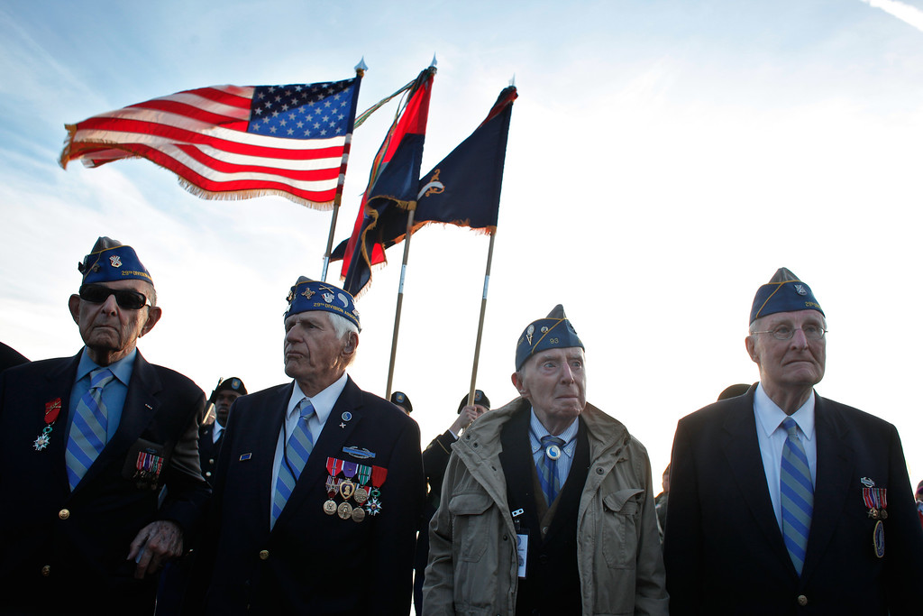 . From left, World War II veterans of the U.S. 29th Infantry Division, Hal Baumgarten, 90 from Pennsylvania, Steve Melnikoff, 94, from Maryland, Don McCarthy, 90 from Rhode Island, and Morley Piper, 90, from Massachusetts, attend a D-Day commemoration, on Omaha Beach, western France , (AP Photo/Thibault Camus)