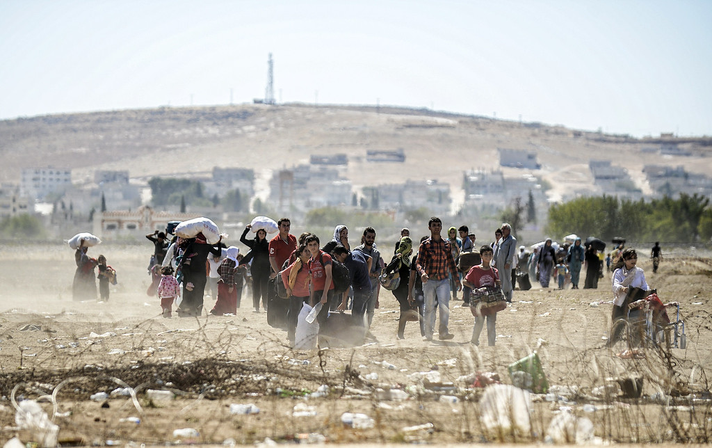 ". Syrian Kurdish families carry their belongings after they crossed the border between Syria and Turkey near the southeastern town of Suruc in Sanliurfa province, on September 20, 2014. Several thousand Syrian Kurds began crossing into Turkey on September 19 fleeing Islamic State fighters who advanced into their villages, prompting warnings of massacres from Kurdish leaders. Turkey on September 19 reopened its border with Syria to Kurds fleeing Islamic State (IS) militants, saying a ""worst-case scenario\"" could drive as many as 100,000 more refugees into the country. BULENT KILIC/AFP/Getty Images"