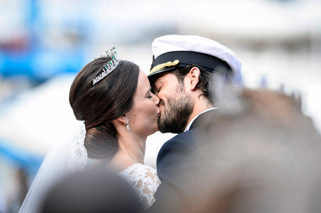 . Sweden\'s  Prince Carl Philip kisses his bride, Sofia Hellqvist in a carriage, after their wedding ceremony,  in Stockholm, Sweden,  Saturday, June 13, 2015.  The only son of King Carl XVI Gustaf and Queen Silvia has married his Swedish fiancee in a lavish ceremony in Stockholm. Prince Carl Philip and the former reality starlet and model Sofia Hellqvist, 30, tied the knot Saturday at the Royal Palace chapel before five European queens, a Japanese princess and dozens of other blue-blooded guests. The couple engaged in June 2014.  (Pontus Lundahl / TT via AP)