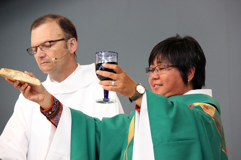 The Rev. Teresita Valeriano presides during communion. Assisting with worship is Thomas Madden.