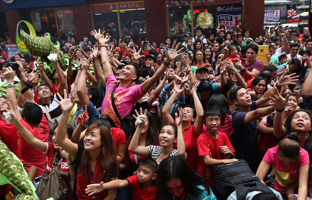 . Filipinos try to catch candies and coins  thrown by store workers from a balcony  as they mark the Chinese New Year in  Binondo Chinatown district of Manila, Philippines, 31 January 2014. Filipino-Chinese communities welcomed the Year of the Horse  on the Chinese New Year, holding various activities and practices traditionally believed to bring good fortune.  EPA/DENNIS M. SABANGAN
