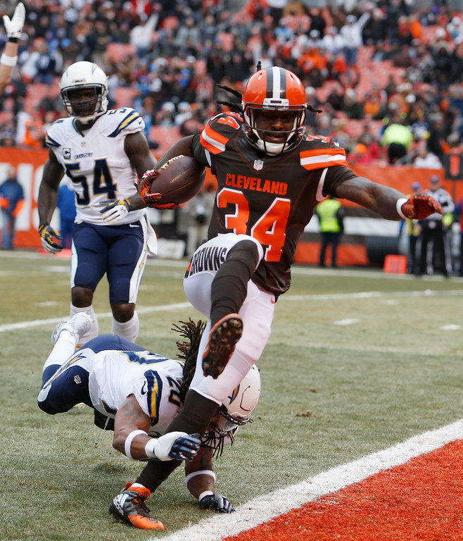 . Cleveland Browns running back Isaiah Crowell scores after rushing 8-yards as San Diego Chargers free safety Dwight Lowery misses a tackle in the first half of an NFL football game, Saturday, Dec. 24, 2016, in Cleveland. (AP Photo/Ron Schwane)