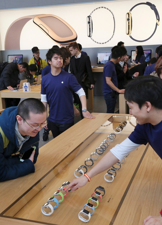 . A customer looks at models of Apple Watch displayed in a glass case at an Apple Store in Tokyo as Apple Watch made its debut Friday, April 10, 2015. Customers were invited to try them on in stores and order them online. (AP Photo/Koji Sasahara)