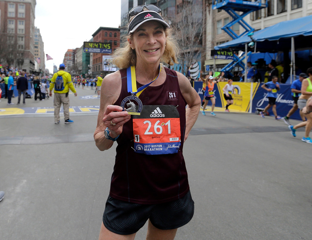 . Kathrine Switzer, who was the first official woman entrant in the Boston Marathon 50 years ago, wears the same bib number and displays her medal after finishing the 121st Boston Marathon on Monday, April 17, 2017, in Boston. (AP Photo/Elise Amendola)