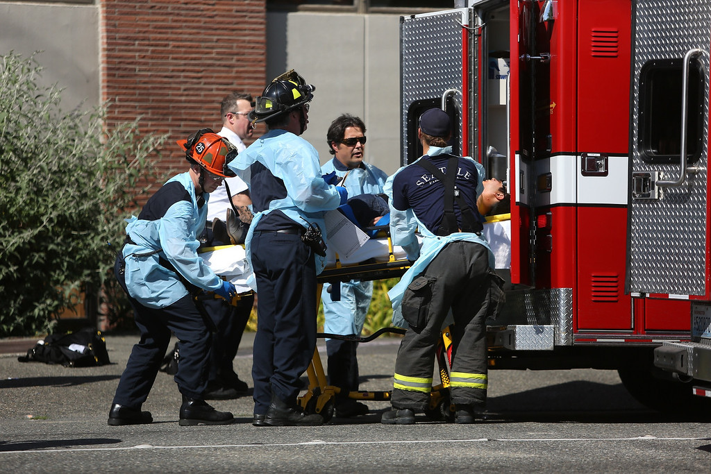 . Seattle firefighters remove a victim from the scene of a shooting at Seattle Pacific University on Thursday, June 5, 2014 in Seattle. About 4,270 students attend the private Christian university, located in a residential neighborhood about 10 minutes from downtown Seattle. (AP Photo/seattlepi.com, Joshua Trujillo)