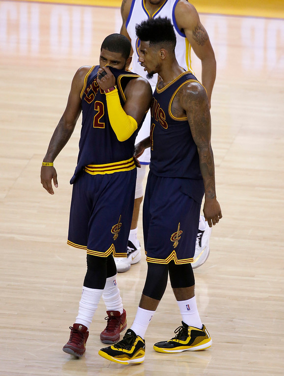 . Cleveland Cavaliers guard Kyrie Irving (2) and guard Iman Shumpert react during the second half of Game 1 of basketball\'s NBA Finals against the Golden State Warriors in Oakland, Calif., Thursday, June 4, 2015. (AP Photo/Eric Risberg)