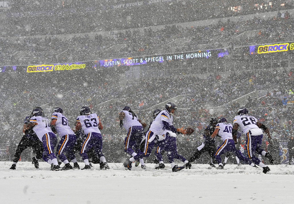 . Snow falls as Minnesota Vikings quarterback Matt Cassel, center, prepares to hand the ball off to running back Adrian Peterson (28) in the first half of an NFL football game against the Baltimore Ravens, Sunday, Dec. 8, 2013, in Baltimore. (AP Photo/Gail Burton)
