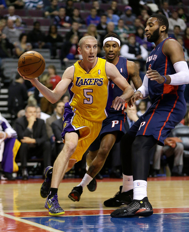 . Los Angeles Lakers guard Steve Blake (5) passes the ball while defended by Detroit Pistons center Andre Drummond (0) during the first quarter of an NBA basketball game at the Palace in Auburn Hills, Mich., Friday, Nov. 29, 2013. (AP Photo/Carlos Osorio)