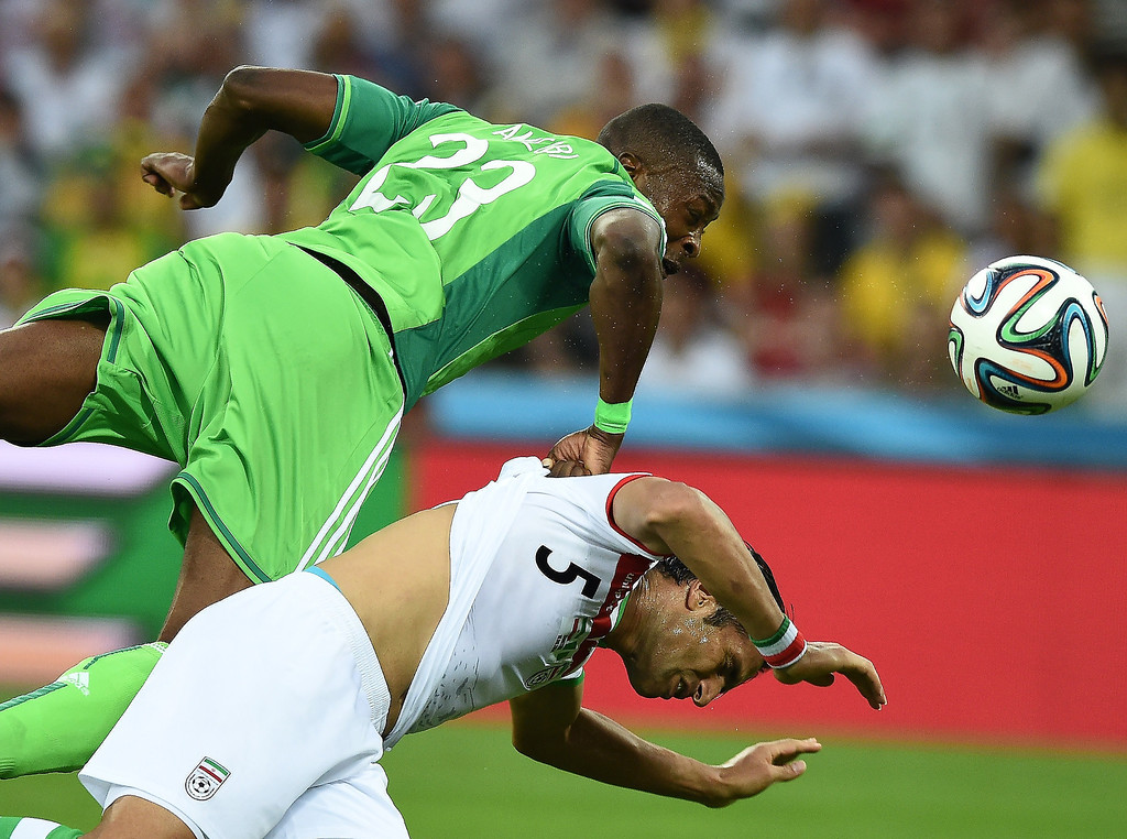 . Nigeria\'s forward Shola Ameobi (L) fights for the ball with Iran\'s defender Amir Hossein Sadeqi during a Group F football match between Iran and Nigeria at the Baixada Arena in Curitiba at the 2014 FIFA World Cup on June 16, 2014.   JEWEL SAMAD/AFP/Getty Images