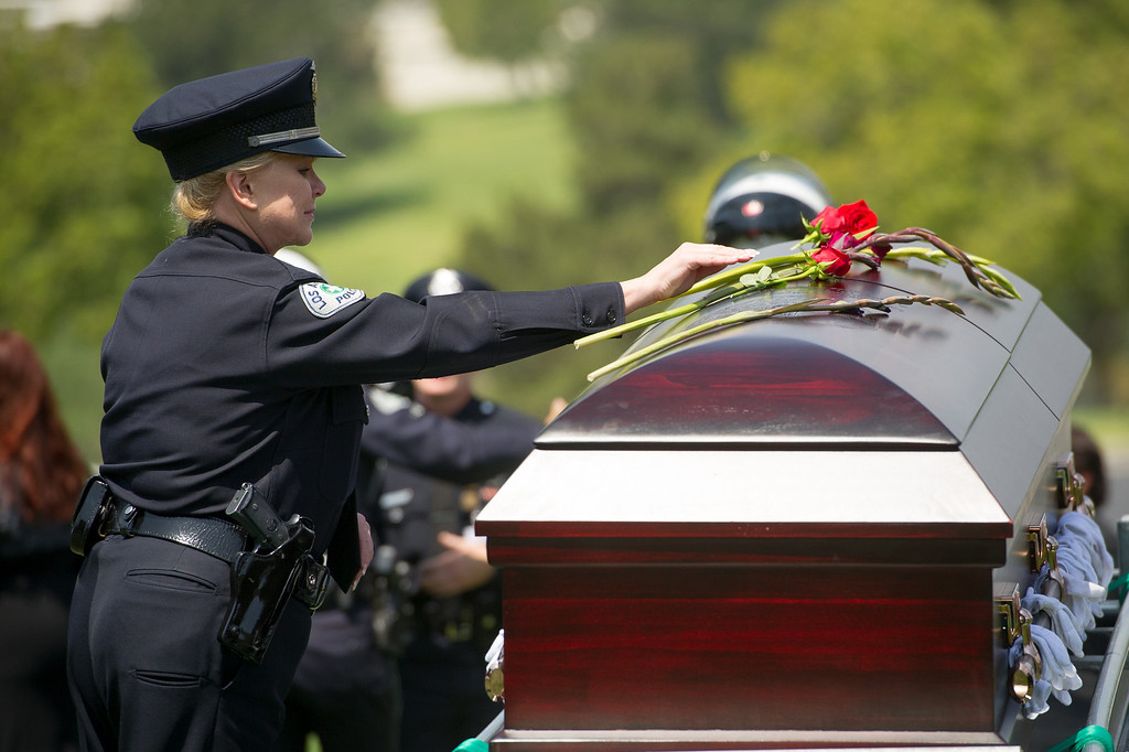 . LAPD Capt. Maureen Ryan, commanding officer of Valley Traffic Division, places a flower on the casket of LAPD officer Chris Cortijo, Tuesday, April 22, 2014, at Forest Lawn Hollywood Hills. (Photo by Michael Owen Baker/L.A. Daily News)