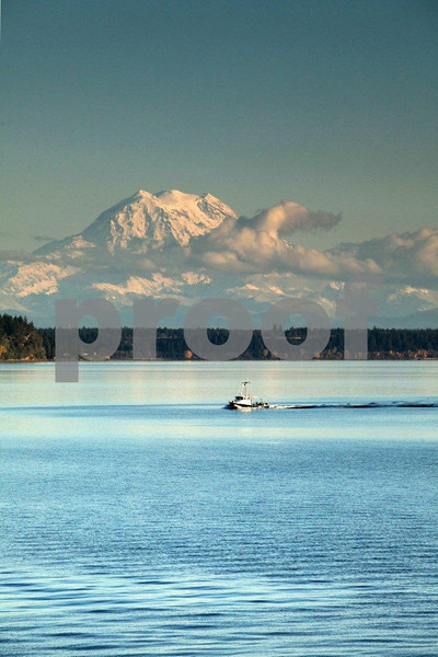 A boater cruises through southern Puget Sound with Mt. Rainier in the background, as seen from Puget Marina near Olypmpia, WA.