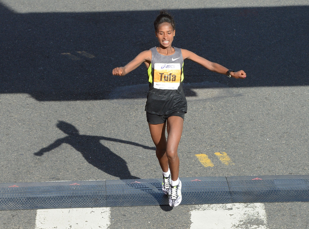 . 2014 ASICS LA Marathon women\'s 2nd place winner Tigist Tufa of Ethiopia,  crosses the finish line in Santa Monica Calif, with a time of 2: 28:04.   Sunday, March 9,  2014.   (Photo by Stephen Carr / Daily Breeze)