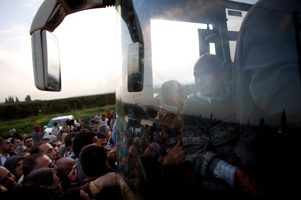 . Palestinians push their way on board a bus as a new line is made available by Israel to take Palestinian laborers from the Israeli army crossing of Eyal, near the West Bank town of Qalqilya, into Israeli cities on March 4, 2013. The new line service to ferry Palestinian workers from the West Bank to Israel, encouraging them to use it instead of traveling with Israeli settlers on a similar route.  (Photo by Uriel Sinai/Getty Images)