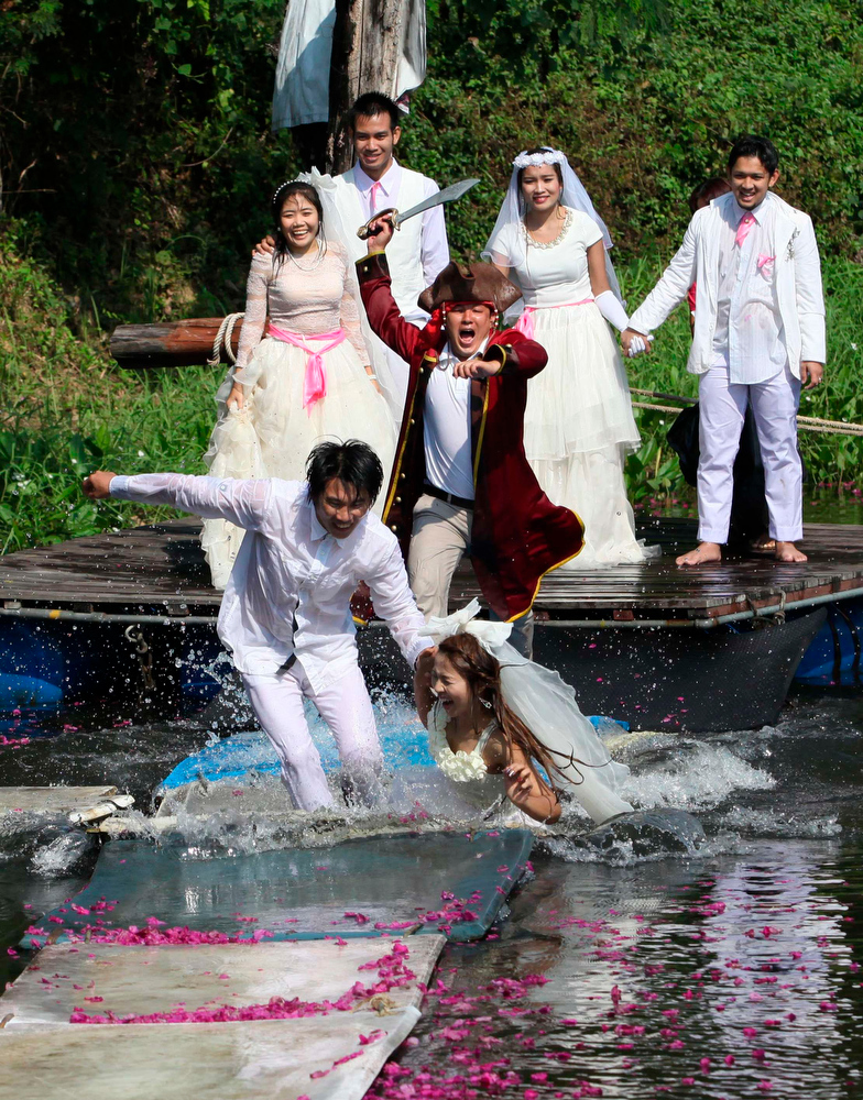 Description of . Thai groom and bride, Sopon Sapaotong, (front L), 41 and Chutima Imsuntear (front R), 37, run to escape a man dressed as a pirate as (behind L-R) Rungnapa Panla, 30, Sorawich Changtor, 28, Rangsiyawong, 27, and Prasit Rangsiyawong, 29, look on during a wedding ceremony ahead of Valentine's Day in Prachin Buri province, east of Bangkok February 13, 2013. Three Thai couples took part in the wedding ceremony arranged by a Thai resort that aimed to strengthen the relationships of the couples by doing fun activities.  REUTERS/Kerek Wongsa