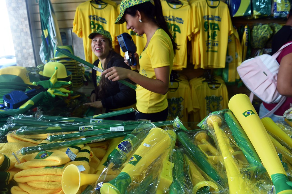. People look at Brazilian paraphernalia in a shop in Itu on June 11, 2014 ahead the 2014 FIFA World Cup in Brazil. AFP PHOTO / RODRIGO ARANGUA/AFP/Getty Images