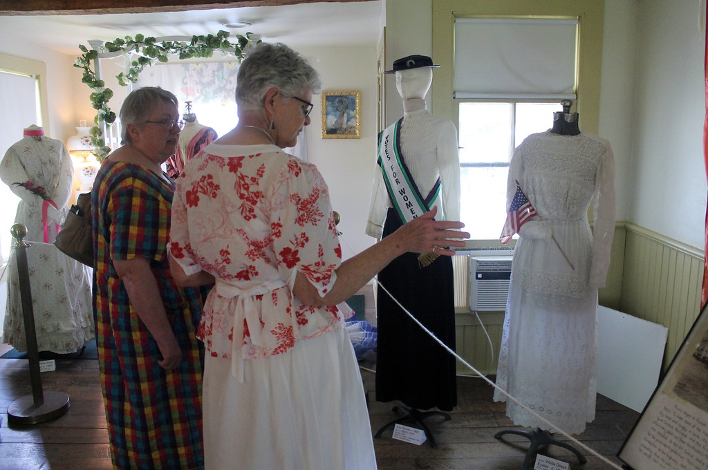 ". Margaret Khairallah of Burton looks over the fashions from the suffrage era with Textile committee co-chair Carmen Kulgoske during the grand opening of the Summer Vintage Fashion exhibit at Century Village in Burton on June 19. The exhibit will remain open on Fridays from noon until 4 p.m. through Oct. 14. Special tours for groups are available by appointment. Call the Geauga County Historical Society at 440-834-1492 for more information, or visit <a href=""http://centuryvillagemuseum.org/\"">centuryvillagemuseum.org</a>. (photo credit: Kristi Garabrandt � The News-Herald)"