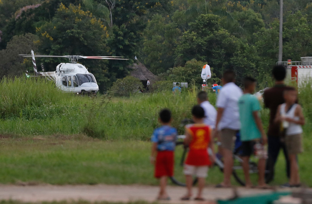 . A helicopter believed to be carrying one of the boys rescued from the flooded cave lands in Chiang Rai as divers continue to extract the remaining boys and their coach trapped at Tham Luang cave in the Mae Sai district in Chiang Rai province, northern Thailand, Tuesday, July 10, 2018. Thai Navy SEALs say all 12 boys and their coach were rescued from the cave, ending an ordeal that lasted more than 2 weeks. (AP Photo/Vincent Thian)