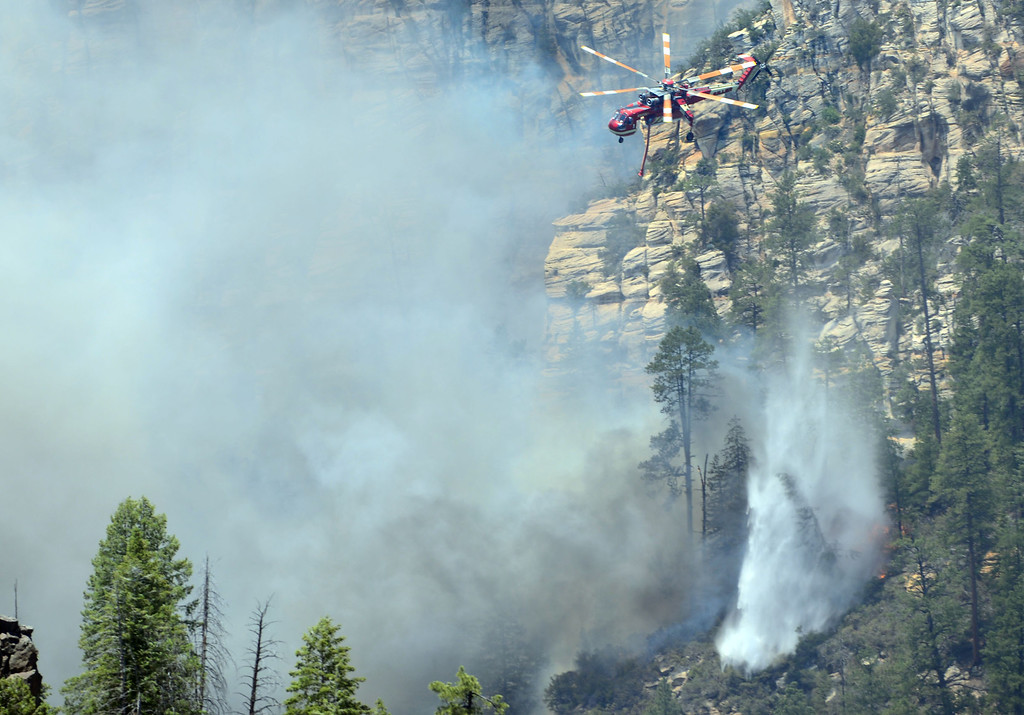 . A firefighting helicopter drops water on a forest fire in Oak Creak Canyon in Sedona, Az., on Thursday May 22, 2014. The human-caused Slide Fire started Tuesday and had burned 7 1/2 square miles in and around Oak Creek Canyon, a scenic recreation area along a highway between Sedona and Flagstaff that normally would be teeming with tourists as the Memorial Day weekend approaches. (AP Photo/Vyto Starinskas)
