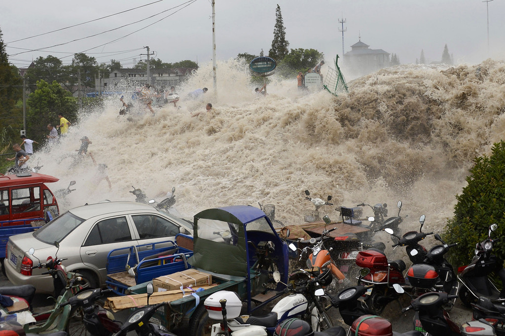 . In this Thursday Aug. 22, 2013 photo, spectators flee as waves created by a tidal bore crash over a barrier on the Qiantang river at Haining, in east China\'s Zhejiang province. About 30 people were injured when they were caught too close to the river while viewing the annual tidal bore, which occurs when sea water from an unusually high tide funnels into the river, creating high waves. (AP Photo)