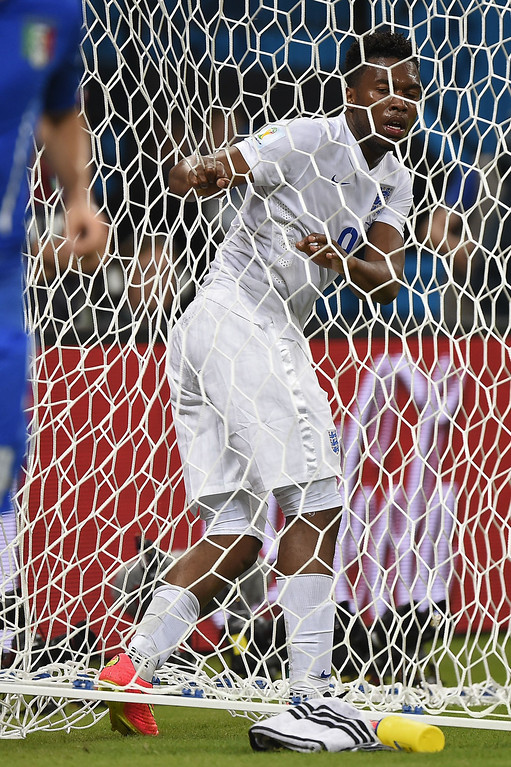 . England\'s forward Daniel Sturridge grabs the goal net after a goal attempt during a Group D football match between England and Italy at the Amazonia Arena in Manaus during the 2014 FIFA World Cup on June 14, 2014.  AFP PHOTO / FABRICE COFFRINI