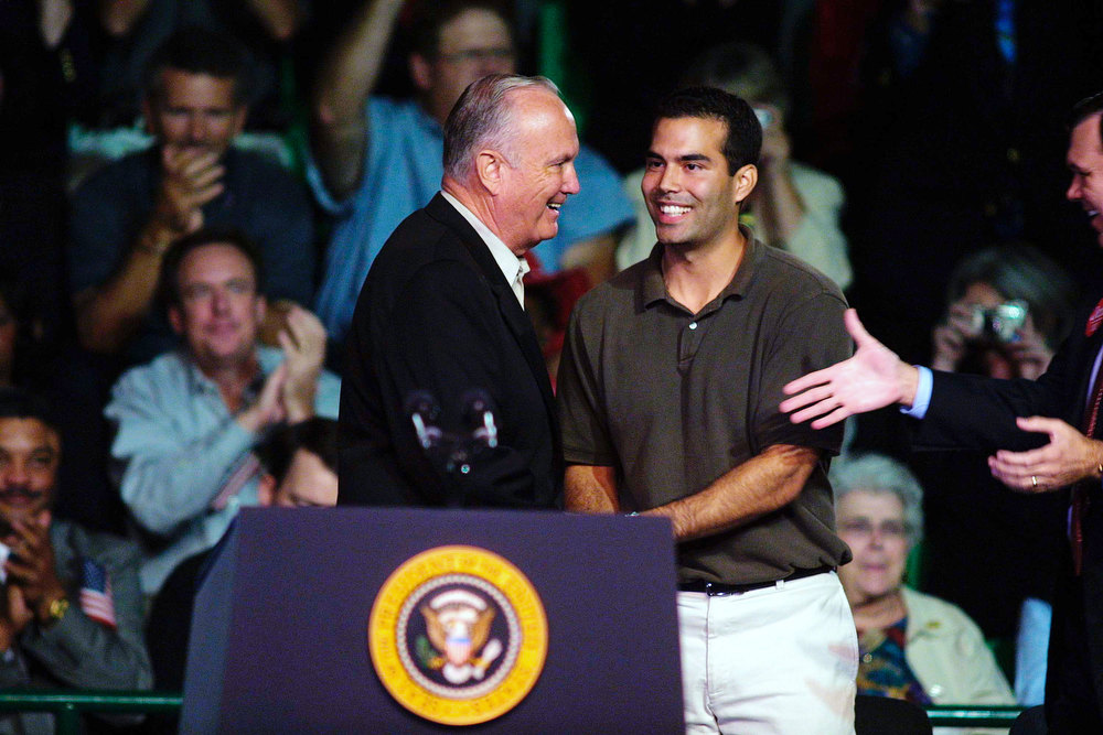 Description of . Retired General Norman Schwarzkopf (L) and George P. Bush, the son of Florida Gov. Jeb Bush, shake hands before President George W. Bush's remarks November 2, 2002 at the University of South Florida Sundome in Tamp, FL. President Bush was campaigning for his brother, Florida Governor Jeb Bush, who is running for re-election against Democrat Bill McBride.  (Photo by Chris Livingston/Getty Images)