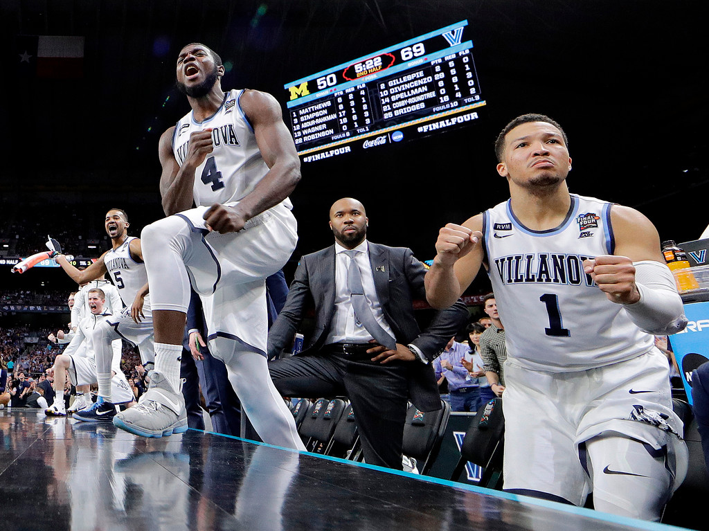 . Villanova\'s Jalen Brunson (1), Eric Paschall (4) and players on Villanova bench react to a 3-point basket during the second half in the championship game of the Final Four NCAA college basketball tournament against Michigan, Monday, April 2, 2018, in San Antonio. (AP Photo/David J. Phillip)