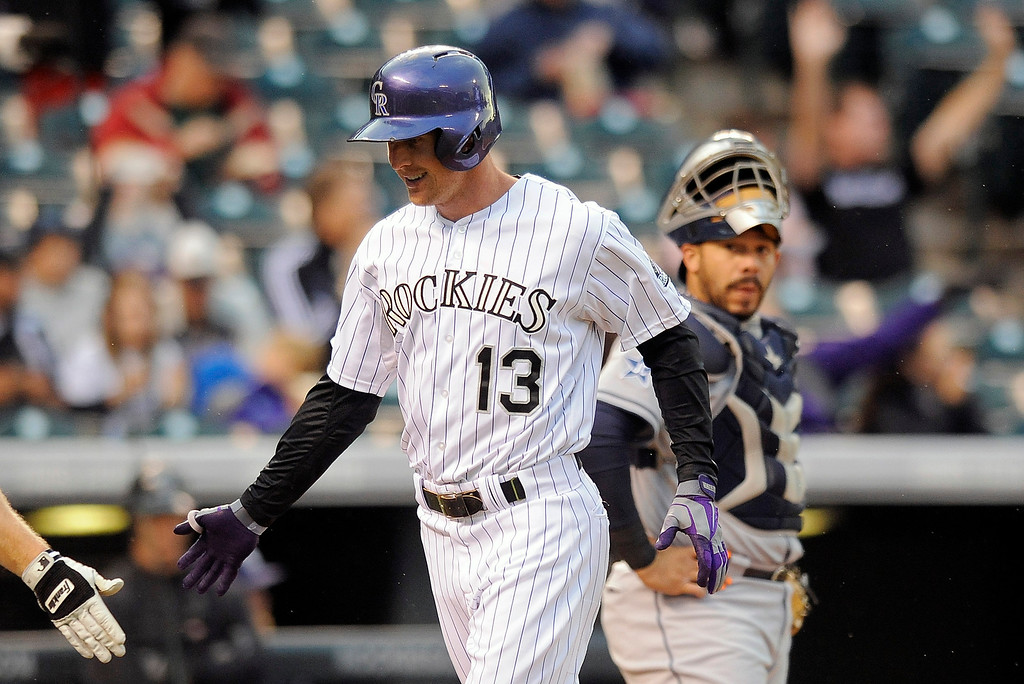 . Colorado Rockies Drew Stubbs, center, is congratulated by Justin Morneau as San Diego padres catcher Rene Rivera, right, watches after Stubbs hit a solo home run in the first inning of a baseball game Friday, Sept. 5, 2014, in Denver. (AP Photo/Chris Schneider)