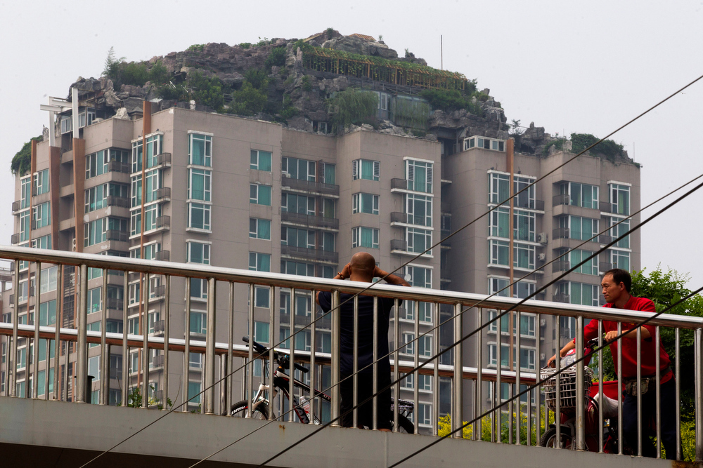 . A man looks at a roof top villa with binoculars from an overhead bridge in Beijing, China, Tuesday, Aug. 13, 2013. Beijing authorities are planning to demolish the bizarre rooftop villa embedded in rocks, trees and bushes that allegedly was built illegally atop a 26-story apartment block in the capital. (AP Photo/Ng Han Guan)