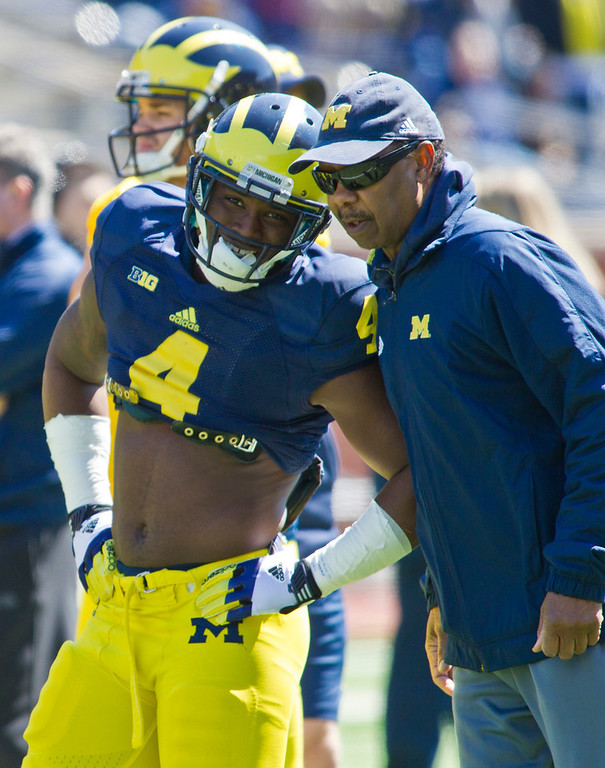 . Michigan running back De\'Veon Smith (4) has words with running backs coach Fred Jackson, right, during the football team\'s annual spring game, Saturday, April 5, 2014, in Ann Arbor, Mich. (AP Photo/Tony Ding)