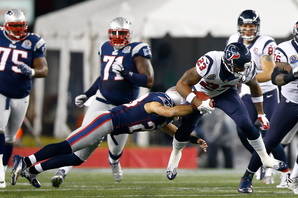 . FOXBORO, MA - DECEMBER 10:  Running back Arian Foster #23 of the Houston Texans runs the ball as he is hit by strong safety Steve Gregory #28 of the New England Patriots in the first half at Gillette Stadium on December 10, 2012 in Foxboro, Massachusetts.  (Photo by Jared Wickerham/Getty Images)