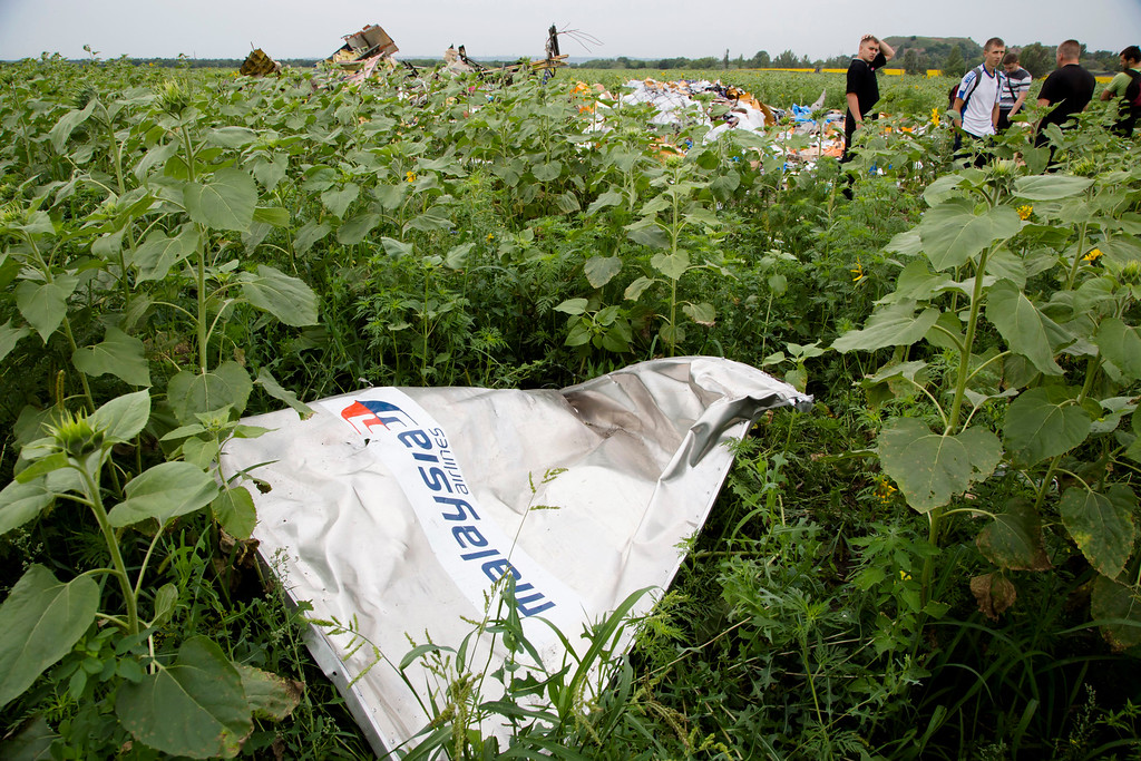 """. A piece of a plane with the sign \""""Malaysia Airlines\"""" lies in the grass as a group of Ukrainian coal miners search the site of a crashed Malaysian passenger plane near the village of Rozsypne, Ukraine, eastern Ukraine Friday, July 18, 2014. Rescue workers, policemen and even off-duty coal miners were combing a sprawling area in eastern Ukraine near the Russian border where the Malaysian plane ended up in burning pieces Thursday, killing all 298 aboard. (AP Photo/Dmitry Lovetsky)"""