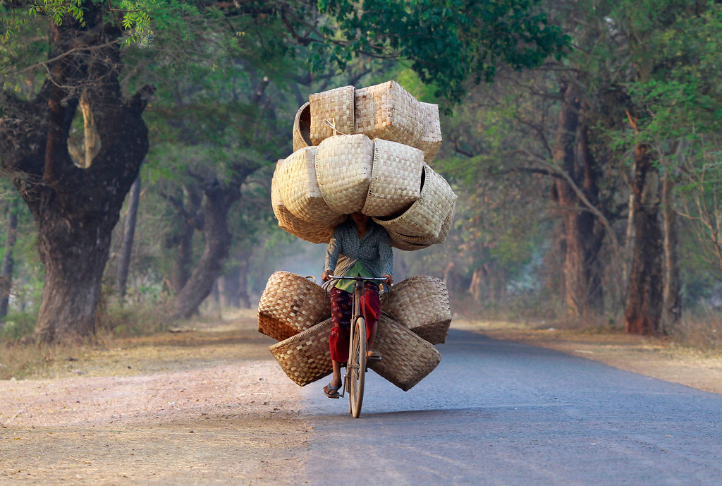 . A woman cycles as she carries baskets to sell in a market near Lapdaung mountain in Sarlingyi township, March 13, 2013. REUTERS/Soe Zeya Tun