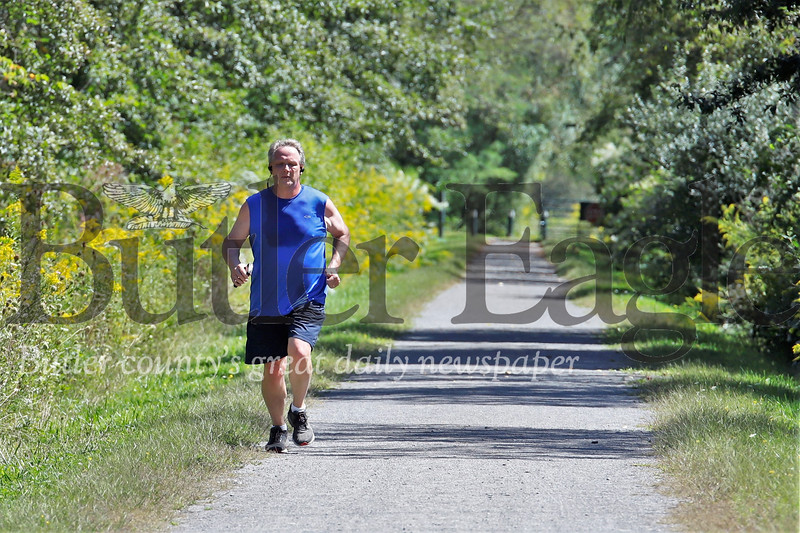 A jogger enjoys the sunshine and solitude of the Butler-Freeport Community Trail Thursday afternoon. Seb Foltz/Butler Eagle 090518