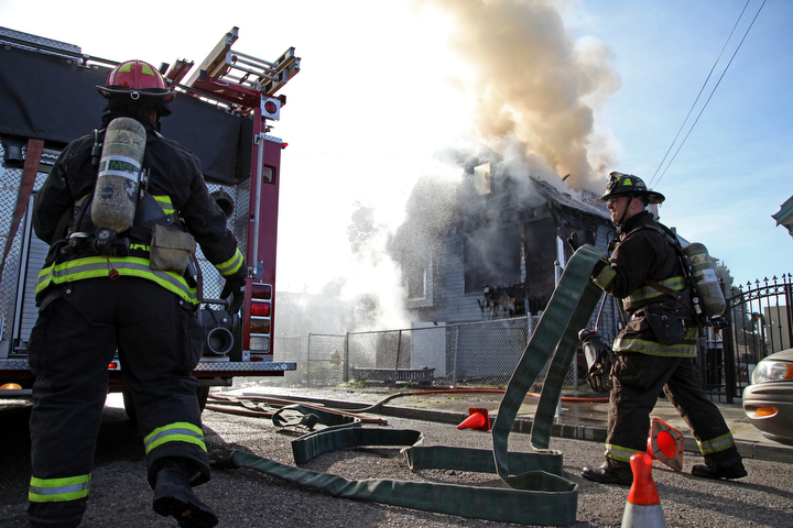 . Oakland firefighters battle a fully involved house fire at a three-story wood-frame house in the 2000 block of East 26th Street that started about 9 a.m. in Oakland, Calif., on Tuesday, Jan. 15, 2013.  The owner was not home when the fire started, said Battalion Chief Jenny Ray.(Laura A. Oda/Staff)
