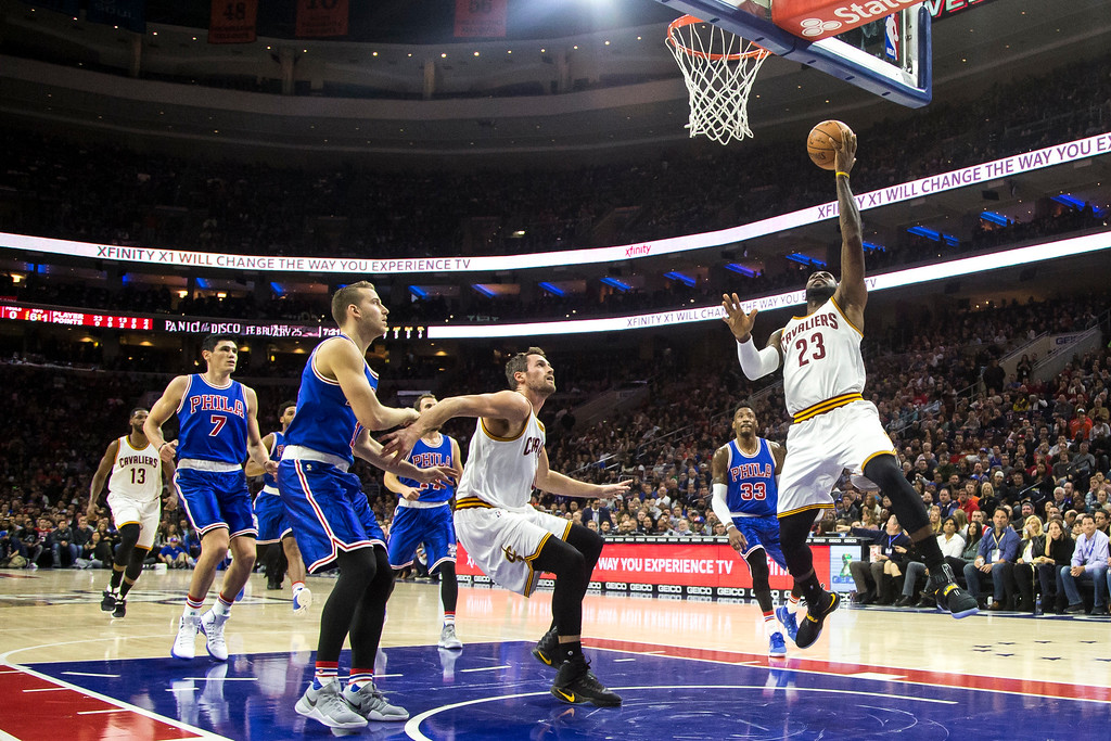 . Cleveland Cavaliers\' LeBron James, right, goes up for the shot as Kevin Love, center, looks out Philadelphia 76ers\' Nik Stauskas, left, during the first half of an NBA basketball game, Saturday, Nov. 5, 2016, in Philadelphia. (AP Photo/Chris Szagola)