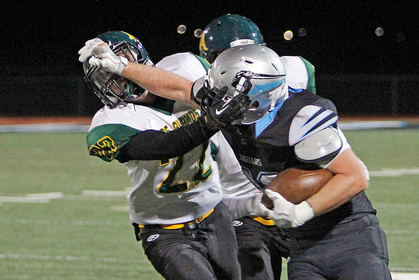 Los Alamos' Ryan Mcneil, number 22, gets strong armed by Capital's Jacob Jiron, number 49, during the first quarter of the Capital High School vs Los Alamos High School football game at Capital on Friday, November 3, 2017. Luis Sánchez Saturno/The New Mexican