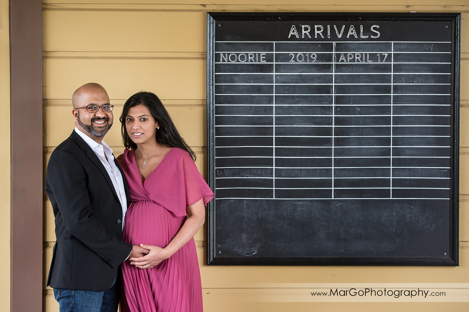 pregnant woman in pink dress and man in dark jacket in front of arrivals board in Ardenwood Historic Farm