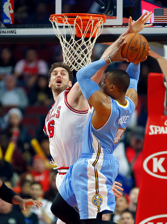 . Chicago Bulls forward Pau Gasol (16) blocks the shot of Denver Nuggets guard Randy Foye (4) during the second half of a pre-season NBA basketball game in Chicago, on Monday Oct. 13, 2014. The Bulls won the game 110-90. (AP Photo/Jeff Haynes)