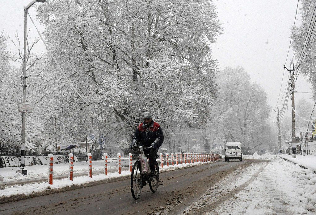. A Kashmiri pedestrians rides his bicycle through slush during a snowfall in Srinagar on December 31, 2013. A cold wave further tightened its grip in Jammu and Kashmir with most places in the state recording sub-zero temperatures. ROUF BHAT/AFP/Getty Images