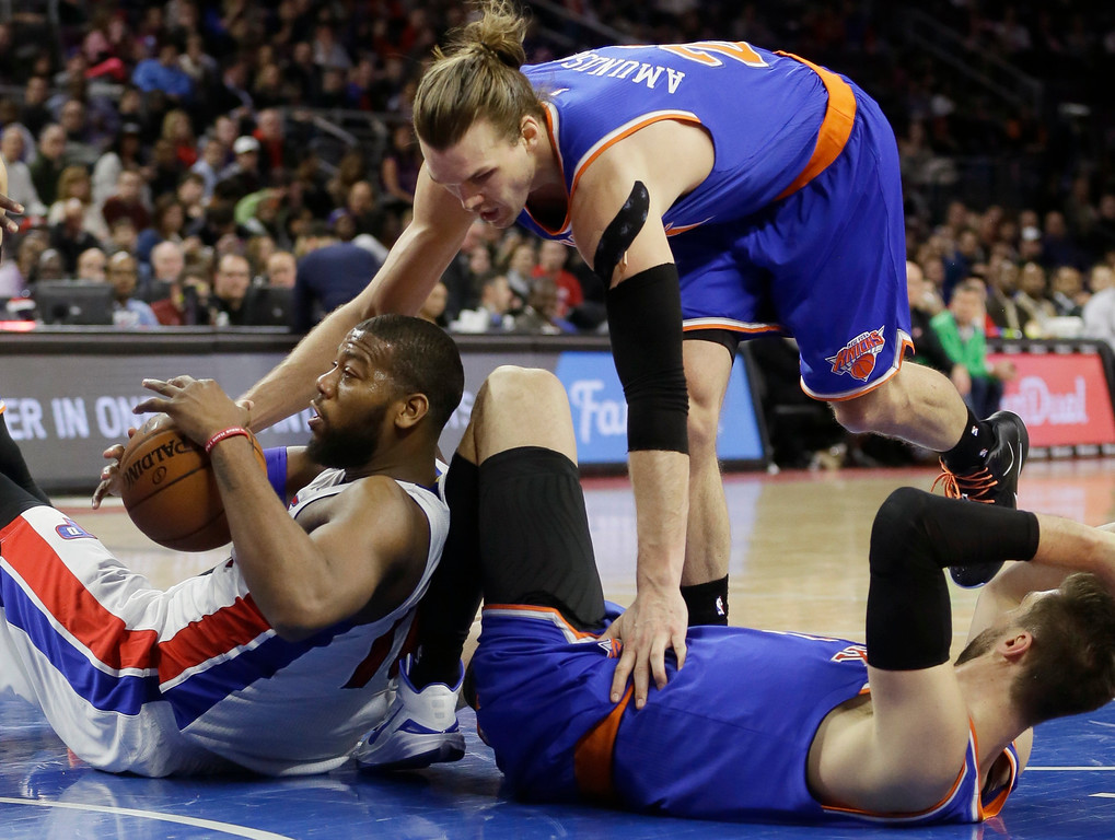 . New York Knicks forward Lou Amundson (21) reaches in on Detroit Pistons forward Greg Monroe, left, as Monroe falls on Knicks center Andrea Bargnani during the second half of an NBA basketball game, Friday, Feb. 27, 2015 in Auburn Hills, Mich. The Knicks defeated the Pistons 121-115 in double overtime. (AP Photo/Carlos Osorio)