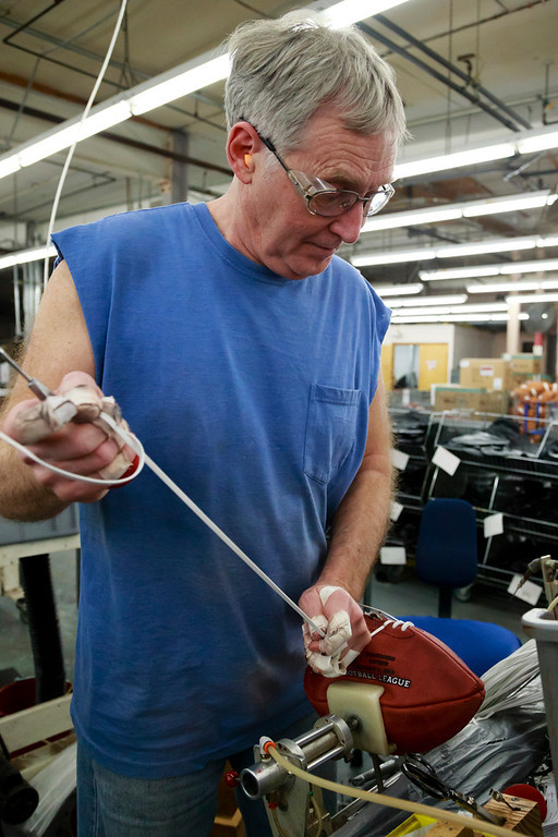 . Doug Falkhauser laces up an official game ball for the NFL football Super Bowl XLVII at Wilson Sporting Goods Co. in Ada, Ohio, Monday, Jan. 21, 2013.  (AP Photo/Rick Osentoski)