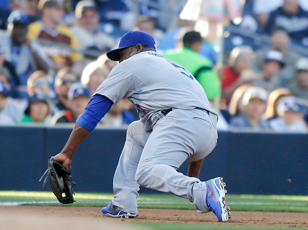 . Los Angeles Dodgers third baseman Juan Uribe makes a backhand stab to get the hard hit ball hit by San Diego Padres\' Chase Headley in the  third inning of the opening game of Major League baseball in the United States Sunday, March 30, 2014, in San Diego. Headley was out at first.  (AP Photo/Lenny Ignelzi)