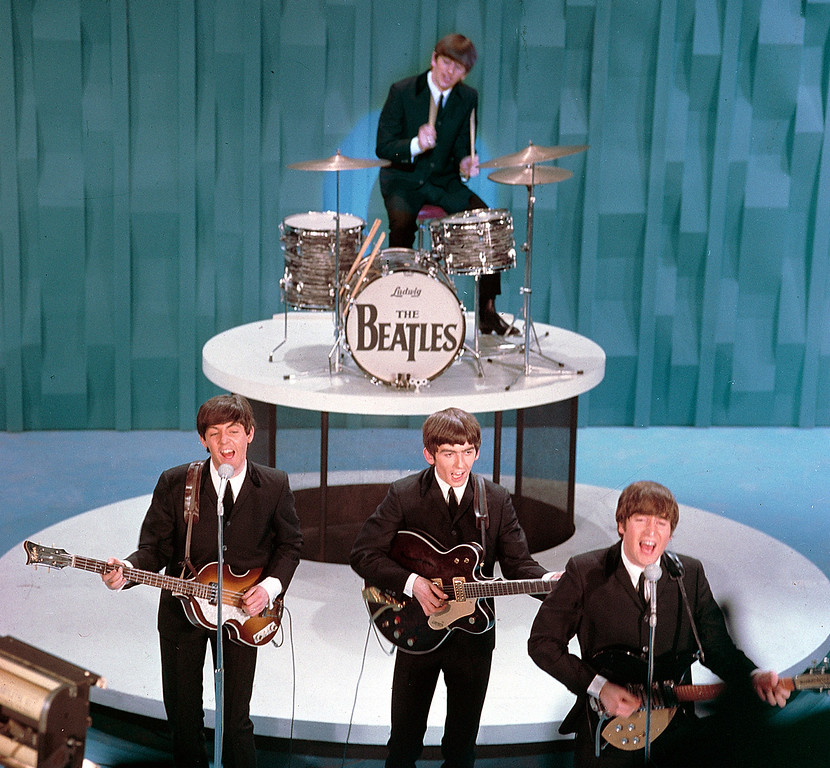 ". The Beatles perform on the ""Ed Sullivan Show"" in New York on February 9, 1964.  From left, front, are Paul McCartney, George Harrison and John Lennon. Ringo Starr plays drums.  (AP Photo)"