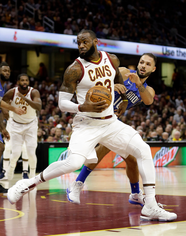 . Cleveland Cavaliers\' LeBron James, left, drives past Orlando Magic\'s Evan Fournier, from France, in the first half of an NBA basketball game, Saturday, Oct. 21, 2017, in Cleveland. (AP Photo/Tony Dejak)