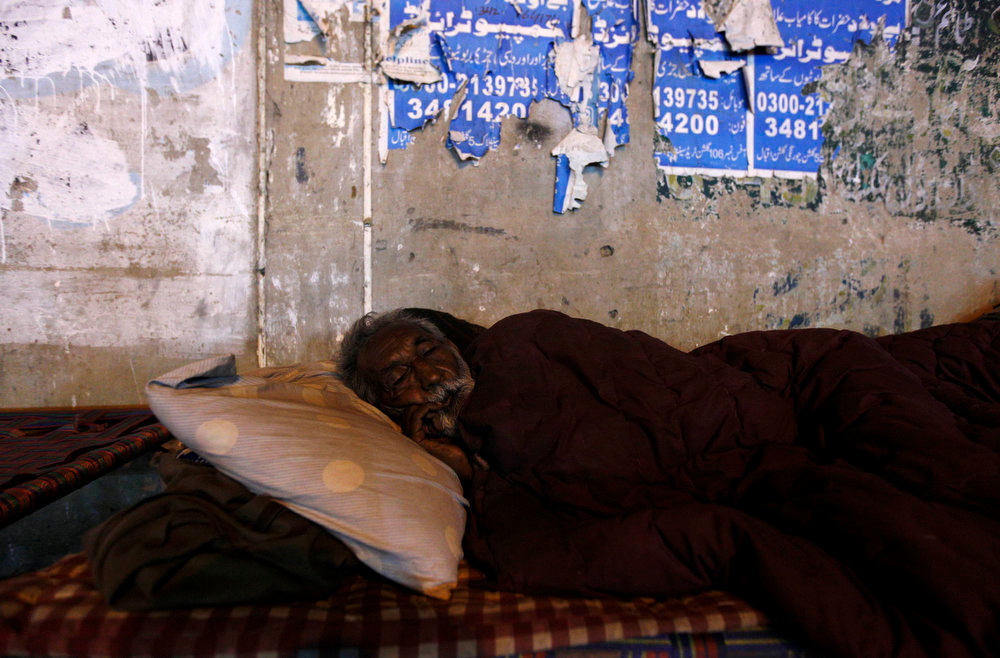 . An elderly man sleeps on a charpoy bed along a road near a railway station in Karachi March 31, 2013. Charpoy bed guesthouses are only set up at night from 9pm to 7am for the homeless, passengers and drivers, charging about 40 Pakistani rupees ($0.40) per night. Picture taken March 31, 2013. REUTERS/Akhtar Soomro