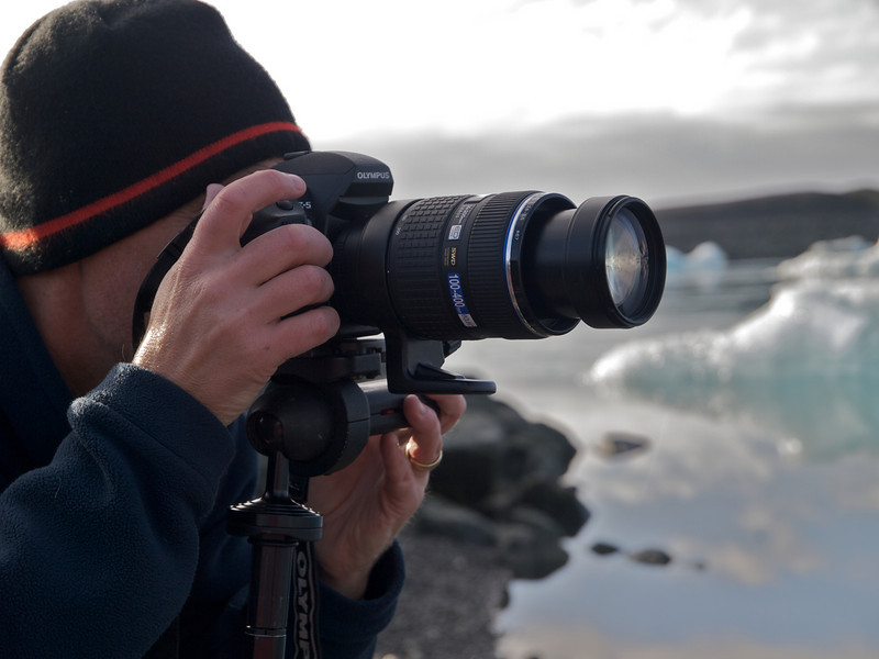 Me shooting with E5 and 50-200mm SWD. The spectacular Jokulsarlon lagoon on the south east side of Iceland. Naturally created by the glacier meltwater from Vatnajokull, which is Europe's largest glacier. The lagoon is full of floating icebergs such as this which are constantly moving. Extremely dangerous too and quite common for them to topple over. As such nobody is allowed to moor up and walk on them. This place was the setting for the James Bond (Pierce Brosnan) film 'Die Another Day' in 2002. The lagoon was deliberately blocked off from the sea (which it connects) for 6 weeks in February in order to prevent salt water inflow (the lagoon is 50/50 salt/fresh water). The lagoon was then closed off for 2 weeks to allow the saltwater to sink thus leaving the freshwater on top to freeze. Once the lagoon was frozen filming commenced :-)