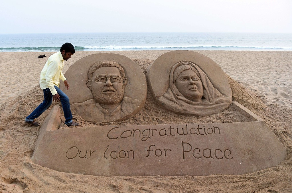 . Indian sand sculptor artist Sudarshan Patnaik gives the final touches to a sand sculpture showing joint Nobel prize winners, Indian Kailash Satyarthi (L) and Pakistan Malala Yousufzai on the beach in Puri, on December 10, 2014.  Pakistani schoolgirl Malala Yousafzai received the Nobel Peace Prize on December 10 in Oslo, Norway as the youngest ever laureate, sharing her award with Indian child rights campaigner Kailash Satyarthi. AFP PHOTO/ Prakash SINGHPRAKASH SINGH/AFP/Getty Images