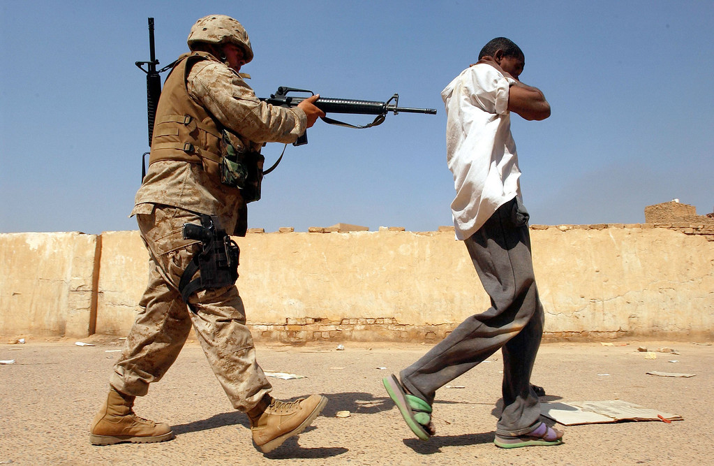 . A U.S. Marine takes away a man suspected of looting April 14, 2003 in Baghdad, Iraq. The Marines began to crack down on looters after Baghdad residents complained of the lack of law and order in the capital. (Photo by Spencer Platt/Getty Images)